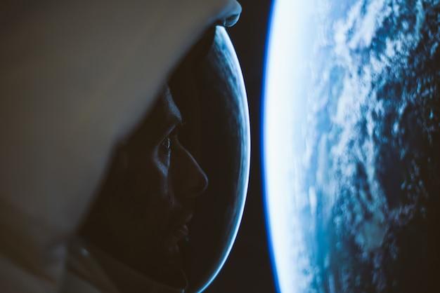 Astronauta olhando espaço profundo, galáxia e planetas da janela de sua cápsula. conceito sobre ciência e exploração espacial