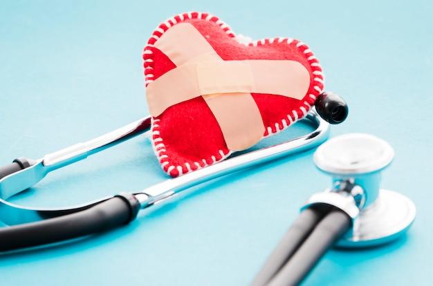 Atadura cruzada sobre o coração de tecido macio vermelho e estetoscópio no fundo azul