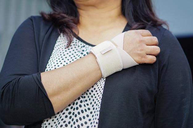 Atadura elástica do uso asiático da senhora em sua mão no escritório.