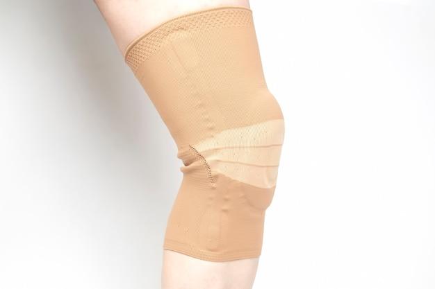 Atadura para fixar o joelho ferido da perna humana em fundo branco. medicina e esportes. tratamento de lesão de membro