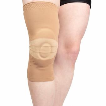 Atadura para fixar o joelho lesionado da perna humana em fundo branco.