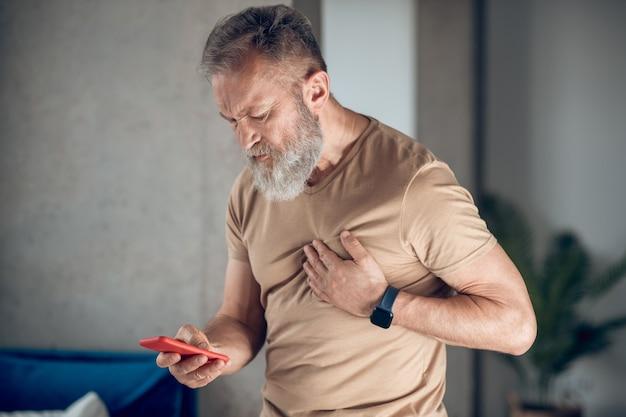Ataque cardíaco. um homem barbudo de meia idade tendo um ataque cardíaco
