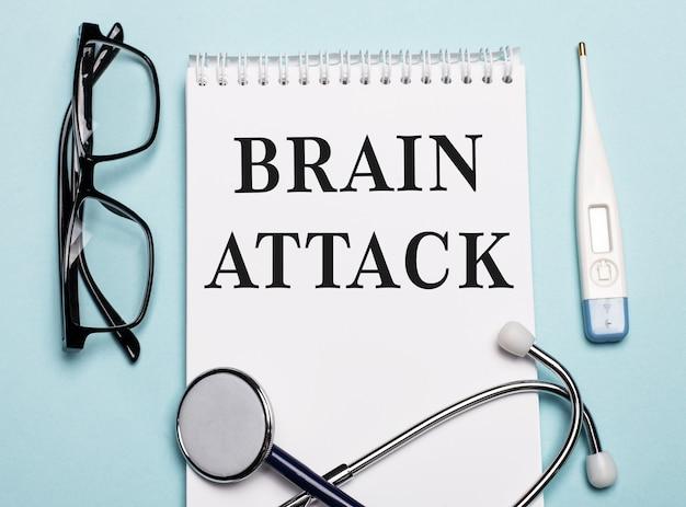 Ataque cerebral escrito em um bloco de notas branco ao lado de um estetoscópio, óculos e um termômetro eletrônico em um fundo azul claro