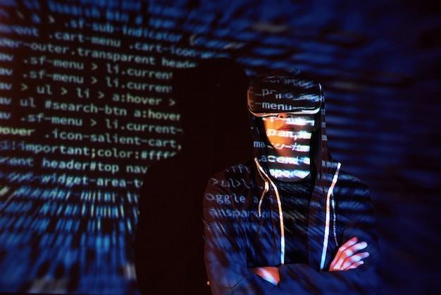 Ataque cibernético com hacker encapuzado irreconhecível usando realidade virtual, efeito de falha digital