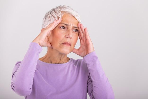 Ataque da enxaqueca monstro. sinusite. infeliz mulher sênior aposentada, segurando sua cabeça com expressão de dor