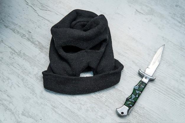 Ataque de homem com faca. o cara com a faca na mão usando um capuz preto. ameaça de uma arma fria. o conceito de crime e roubo. local do crime, cena do crime,