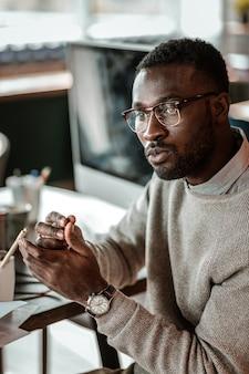 Ataque seus cérebros. homem jovem atento, imerso em pensamentos enquanto está sentado no escritório