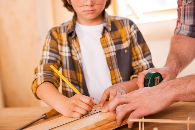 Até o último detalhe. seriousboy fazendo medições na prancha de madeira enquanto seu pai o ajudava