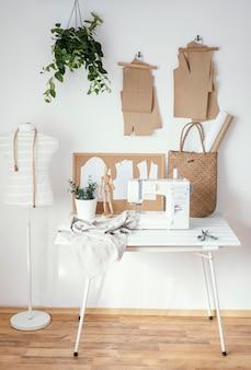 Ateliê de alfaiataria com máquina de costura e mesa
