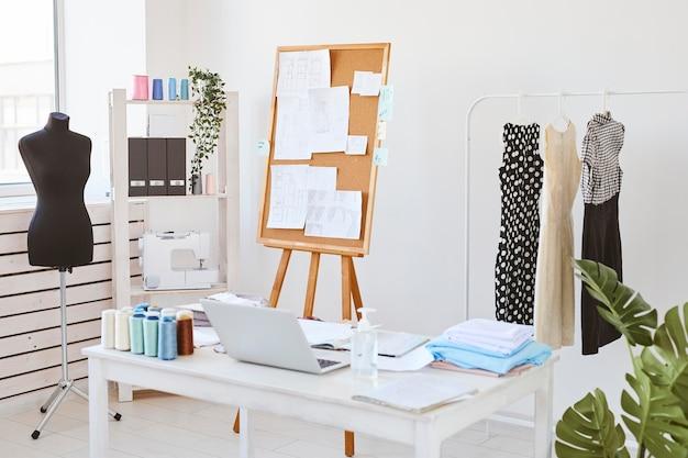 Ateliê de moda com quadro de ideias e mesa com linha de roupas