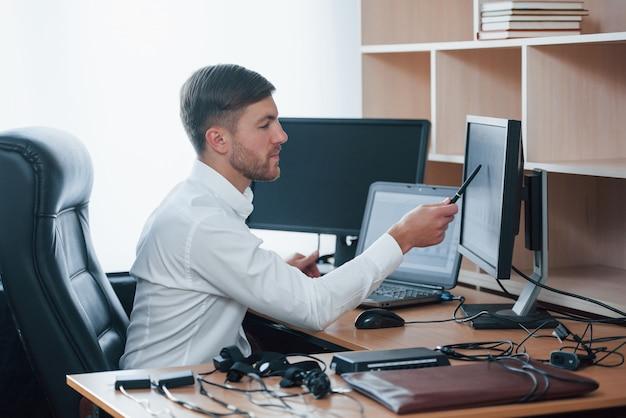 Atenção a esta parte. o examinador de polígrafo trabalha no escritório com seu equipamento detector de mentiras