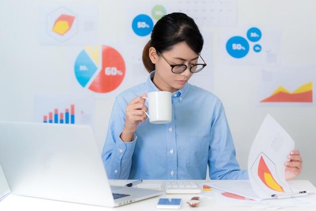 Atenção asiática do pagamento da mulher de negócios ao trabalhar conceitos do negócio e da finança.