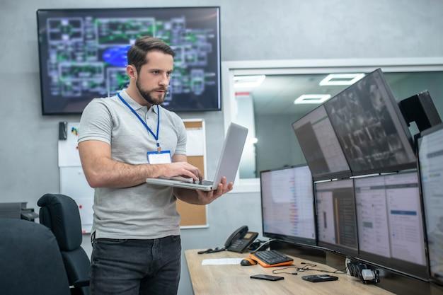 Atenção e foco. atento jovem homem musculoso com crachá e laptop em frente a monitores de computador