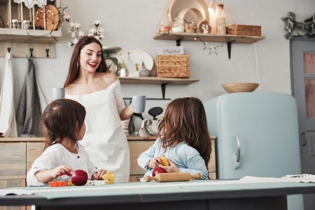 Atenção, eu tenho potáveis deliciosos. jovem mulher bonita dar as crianças bebidas enquanto eles sentados perto da mesa com brinquedos