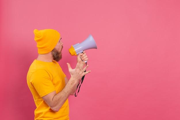 Atenção! homem europeu com megafone apontando o dedo para a direita em fundo rosa