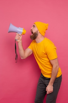 Atenção! homem europeu furioso gritando no megafone no fundo rosa