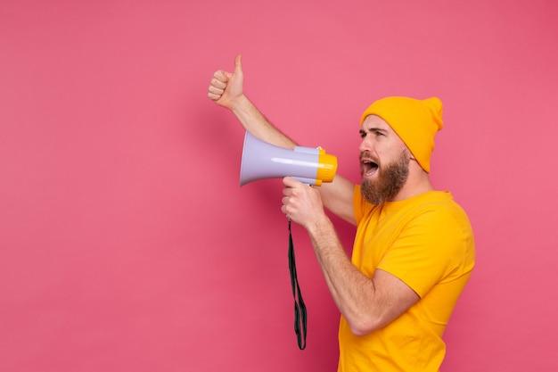 Atenção! homem europeu gritando no megafone no fundo rosa