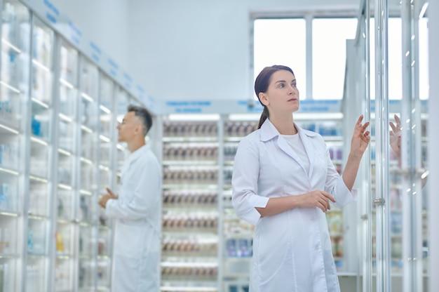 Atenção .. mulher atenciosa com longos cabelos escuros no jaleco branco olhando as prateleiras das drogarias procurando preparação necessária e funcionário