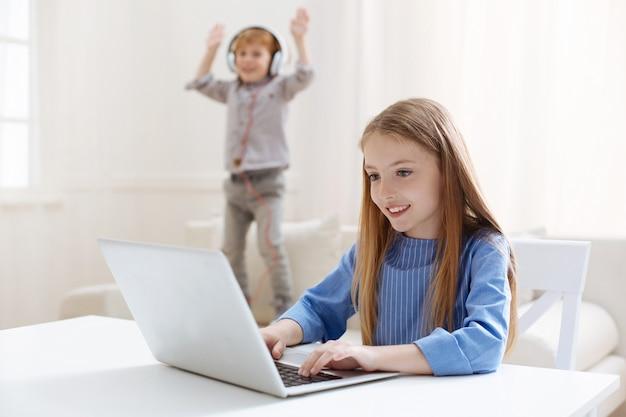 Atenciosa garota talentosa e apaixonada trabalhando em uma redação enquanto seu irmão pulava em um sofá e tentava distraí-la