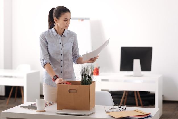 Atenciosa jovem trabalhadora de escritório com a mão na caixa, virando a cabeça em pé perto do local de trabalho