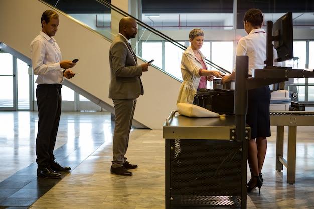 Atendente do check-in da companhia aérea entregando o cartão de embarque ao passageiro