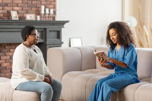 Atendente médico. atendente médico particular sentado na sala de estar lendo livro para paciente idoso de pele escura
