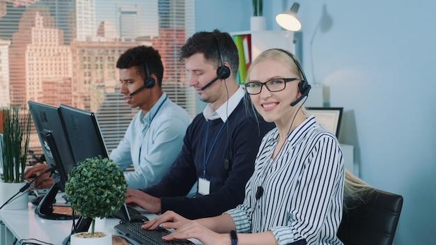 Atendimento ao cliente feminino trabalhando em call center ocupado.
