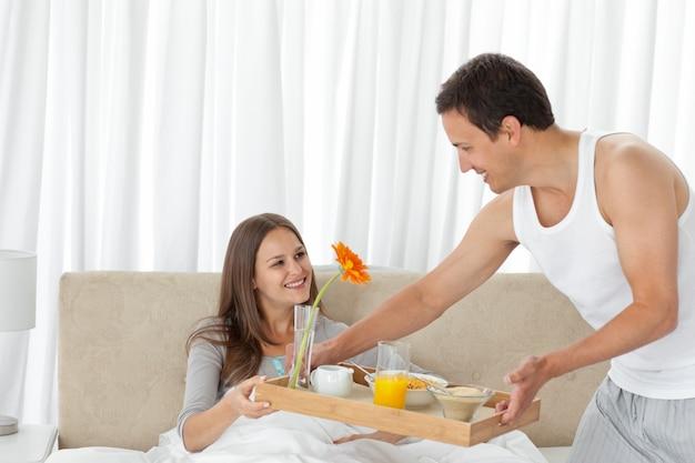 Atento que serve o café da manhã para sua namorada na cama
