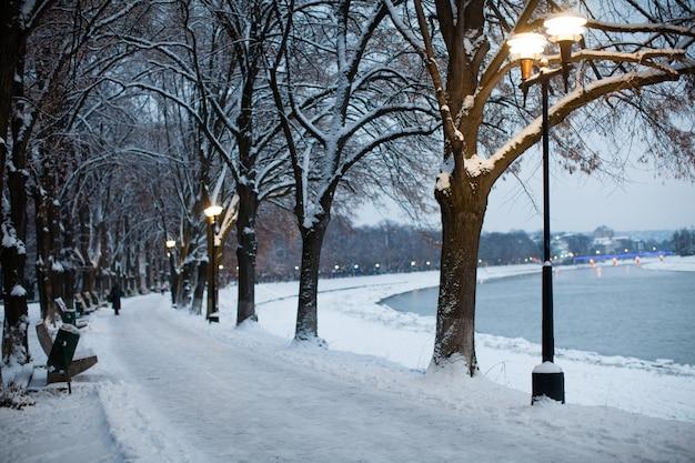 Aterro coberto de neve na cidade à noite. linda paisagem de inverno