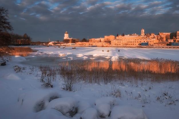 Aterro com pescadores e belos edifícios antigos da cidade de vyborg, na rússia, no meio do século, no pôr do sol de inverno