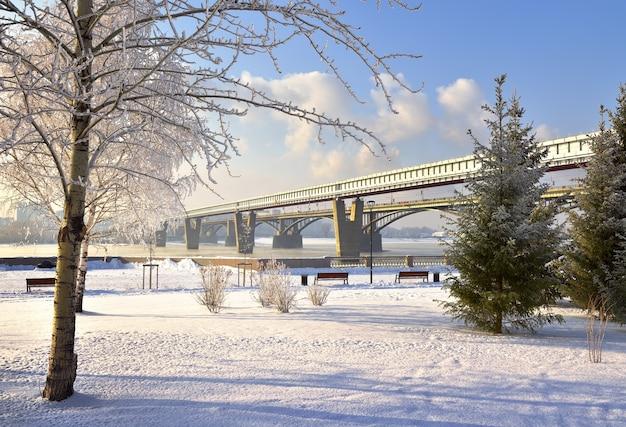Aterro de michael no inverno. a ponte da ponte metropolitana sobre o rio ob leva a uma área montanhosa
