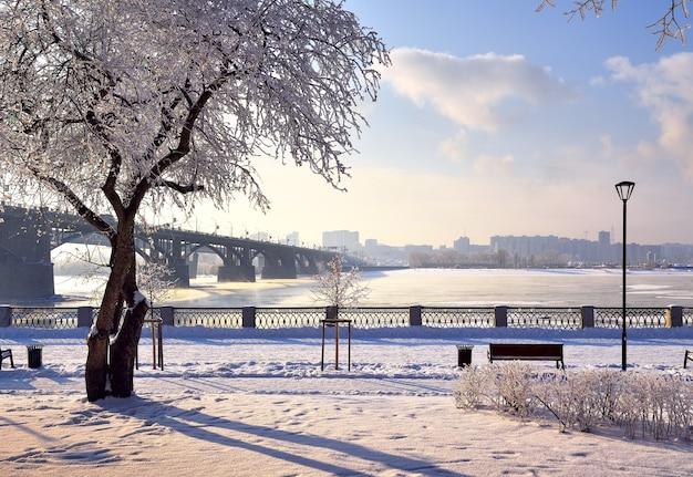 Aterro de michael no inverno. a ponte oktyabrsky sobre o rio ob leva ao distrito de gorsky