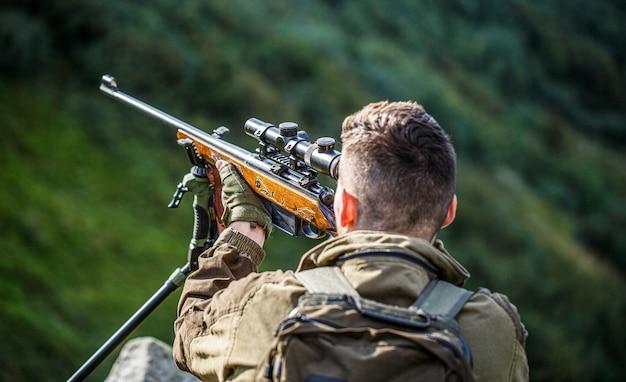 Atirador avistando no alvo, o homem está na caça, caça, caça, rifle, caçador, homem, caça, período