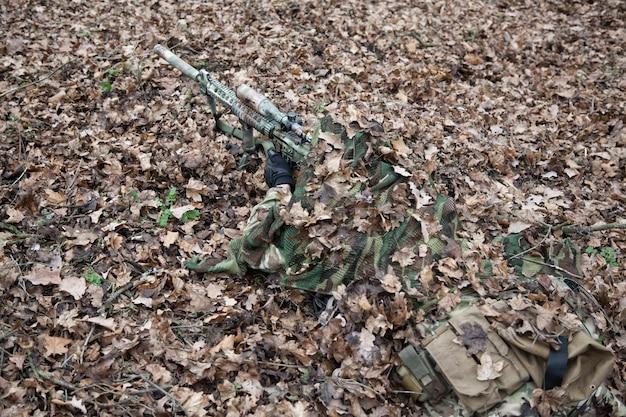 Atirador de elite das forças de elite do exército, atirador de grupo tático, jogador de airsoft deitado no solo na floresta, escondido na folhagem de outono, cobrindo-se com uma capa de camuflagem, procurando alvos através da mira óptica