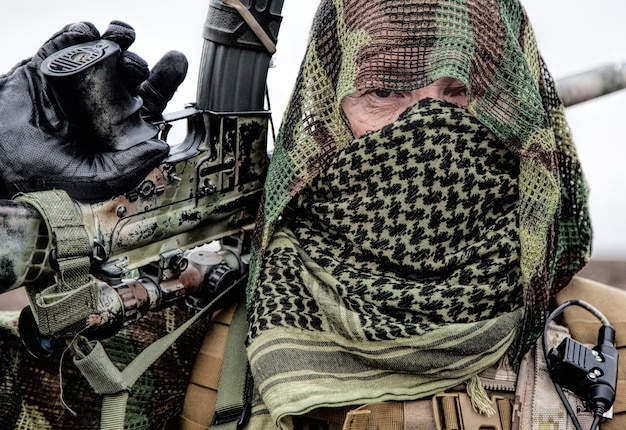 Atirador do exército, jogador de airsoft com uniforme camuflado e carregador de carga, capa de máscara na cabeça, rifle de serviço armado com mira óptica, escondendo rosto com shemagh, em pé no campo, olhando para longe