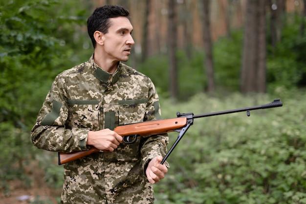 Atirador masculino com época de caça do rifle nas madeiras.