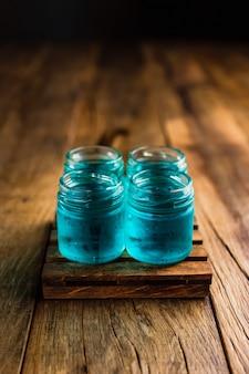 Atiradores alcoólicos de cor azul, ou bebidas atiradas na mesa de madeira, com espaço de cópia
