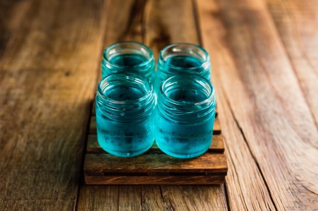 Atiradores alcoólicos de cor azul ou bebidas na mesa de madeira