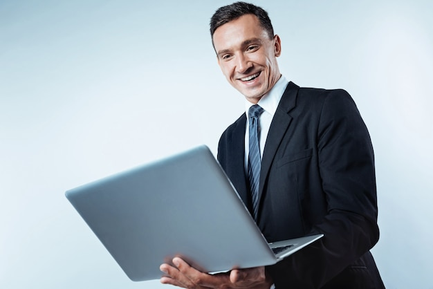 Atitude positiva para o trabalho. tiro de ângulo baixo de um empresário maduro e animado olhando para a tela de um computador com um largo sorriso no rosto enquanto trabalhava no plano de fundo.