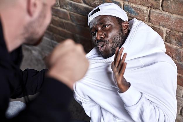 Atividade criminosa, vício, conceito de problema social. homem afro assustado sentado no chão, ameaçado por um rastejador caprino, caucasiano, exigindo dinheiro e outras coisas do homem negro africano