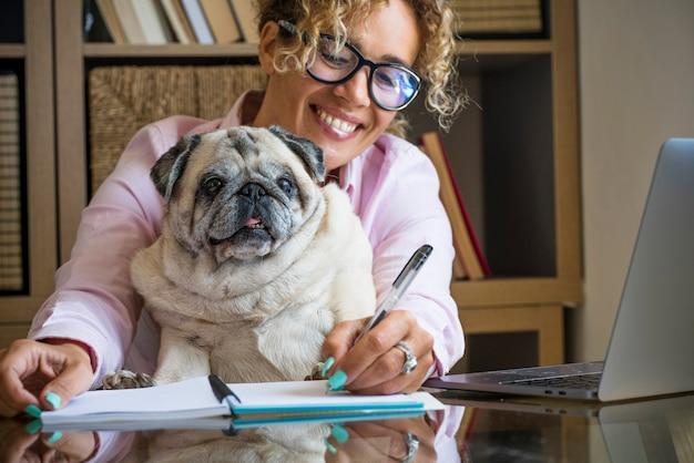 Atividade de escritório em casa de trabalho inteligente, jovem mulher moderna e cachorro juntos - uma pessoa do sexo feminino escreve no caderno e trabalha com o computador, laptop - negócios de estilo de vida alternativo