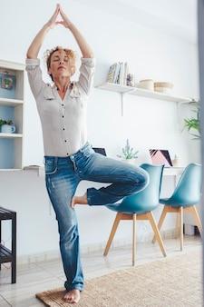 Atividade de exercícios de ioga e bem-estar em casa com uma mulher adulta em roupas casuais, fazendo uma posição equilibrada na sala de estar com o local de trabalho ao fundo - casa de estilo de vida de pessoas modernas