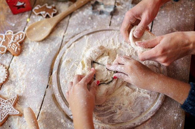 Atividade de férias em família. vista superior das mãos da mãe e da criança fazendo biscoitos de árvore de natal no fundo da mesa de madeira. configuração plana.