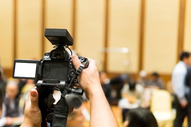 Atividade de gravação de vídeo de fotógrafo com a sala de reunião do evento. fundo desfocado