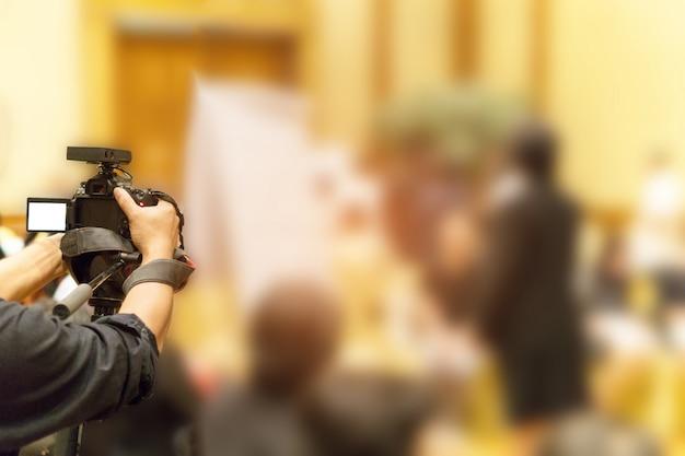 Atividade de gravação de vídeo do fotógrafo dentro da sala de reunião do evento.