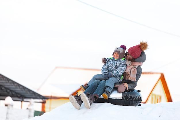 Atividade de inverno para mãe e filho, deslize da colina de neve