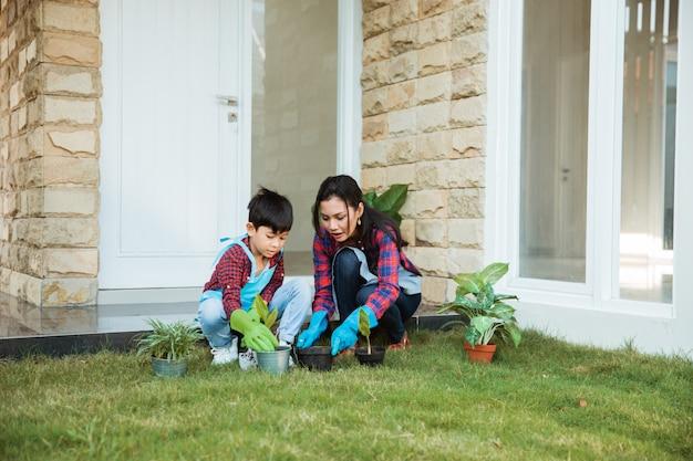 Atividade de jardinagem mãe e filho na frente de sua casa