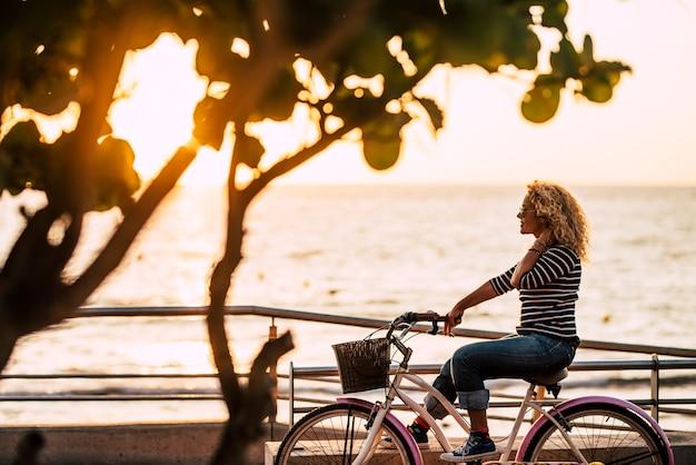 Atividade de lazer ao ar livre para o conceito de pessoas felizes com uma bela mulher adulta loira encaracolada apreciando o pôr do sol andando de bicicleta colorida - mulher ativa na moda procurando o oceano