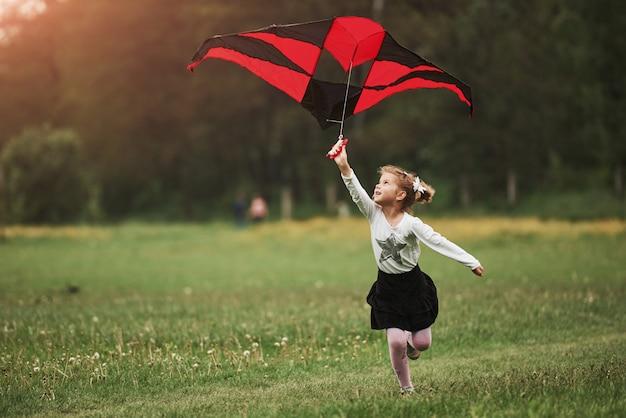 Atividade de lazer. garota feliz com roupas casuais, correndo com a pipa no campo. natureza bela
