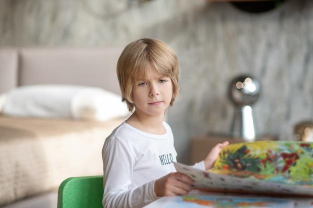 Atividade de leitura. um menino louro lendo uma revista em casa